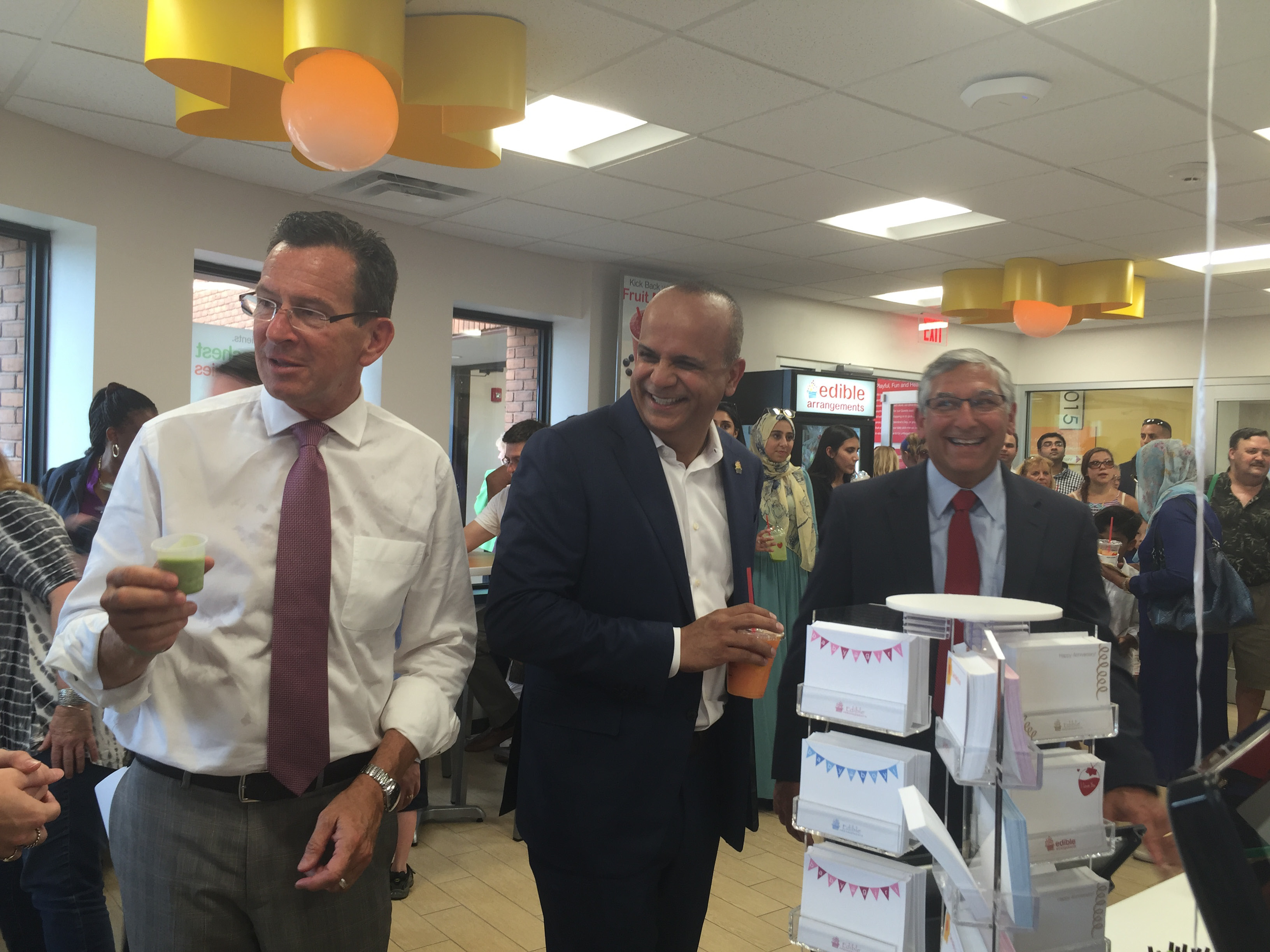 Gov. Dannel P. Malloy, Edible Arrangments founder and CEO Tariq Farid and state Sen. Len Fasano, R-North Haven, enjoy smoothies Wednesday at the grand opening ceremony for Edible Arrangements flagship store at its Barnes Road corporate headquarters in Wallingford. | Leigh Tauss, Record-Journal