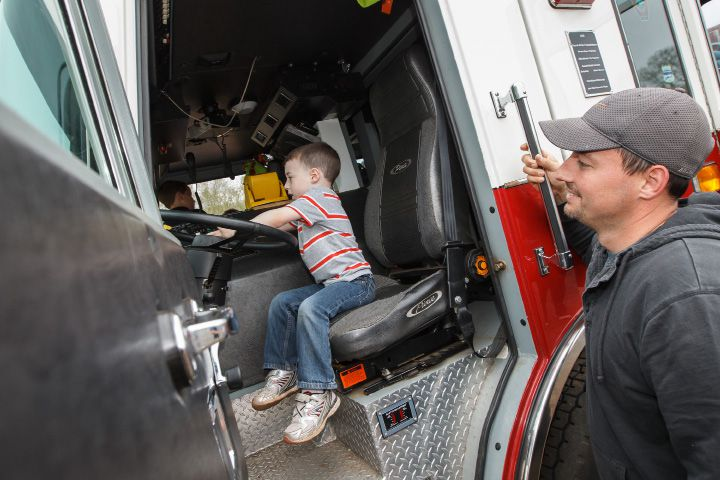 "Gary Smith of Southington watches his son Carter 5 ""steer"" a Southington fire department engine Saturday during a Touch a Truck event at the Southington Drive In May. 9, 2015 