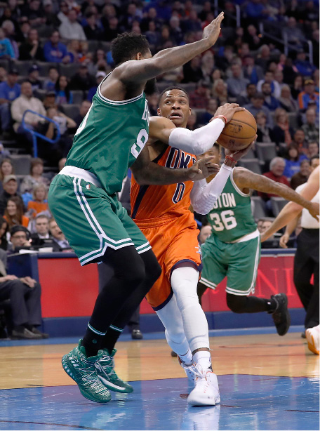 Oklahoma City's Russell Westbrook, right, drives to the basket as Amir Johnson of the Celtics defends during the first half of last night's game in Oklahoma City. | Associated Press