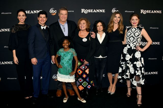 "FILE - In this March 23, 2018 file photo, from left, Whitney Cummings, Michael Fishman, John Goodman, Jayden Rey, Roseanne Barr, Sara Gilbert, Sarah Chalke and Emma Kenney arrive at the Los Angeles premiere of ""Roseanne"" in Burbank, Calif. ABC, which canceled its ""Roseanne"" revival over its star"