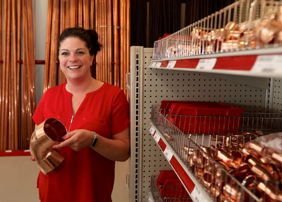 "Jessica Flint, store manager, holds a 4"" copper elbow, one of many supplies available at the the new F.W. Webb Company at 30 Pomeroy Ave. in Meriden, Friday, June 28, 2018. The store is open weekdays 6:30 a.m. to 4:30 p.m.  Dave Zajac, Record-Journal"