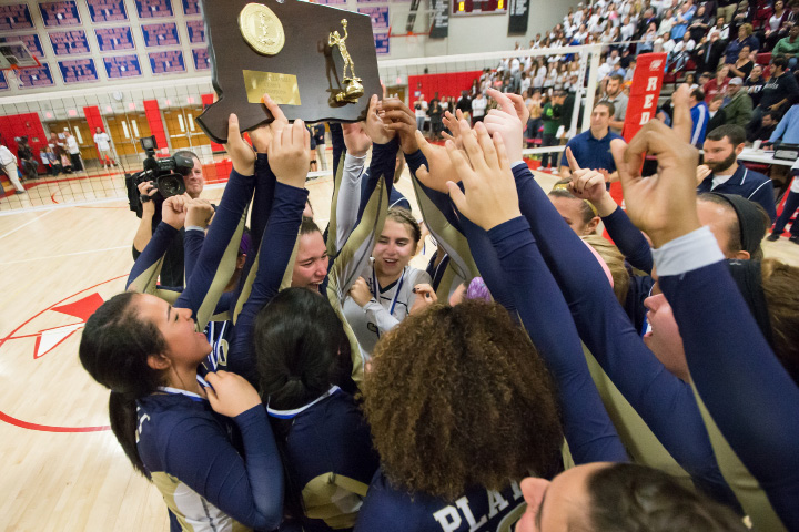 ABOVE: Platt's Gaby Vazquez and her teammates hoist the CIAC Class L girls volleyball plaque Saturday after beating RHAM 3-1 at Berlin High School in Berlin. RIGHT: The state champions pose for posterity. BELOW: Platt students storm the court to join the celebration. More photos at myrecordjournal.com.  | Justin Weekes / For the Record-Journal