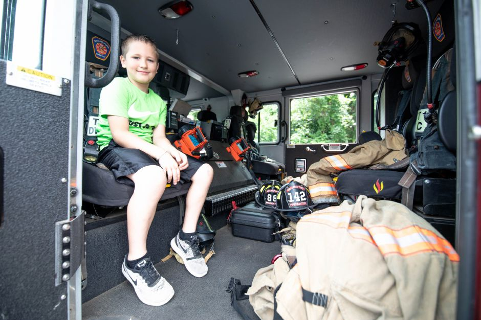 Austin Standish, 9, of Wallingford, sits in the back of Wallingford Engine 1 at the fire department