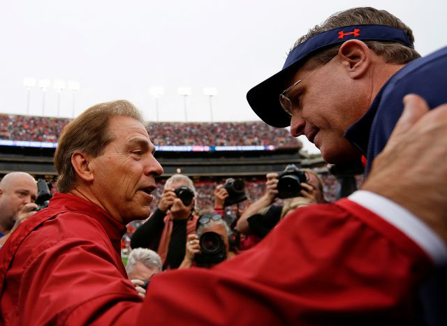 Alabama coach Nick Saban, left, and Auburn coach Gus Malzahn, right, meet in the middle of the field before the Iron Bowl NCAA college football game, Saturday, Nov. 25, 2017, in Auburn, Ala. (AP Photo/Brynn Anderson)