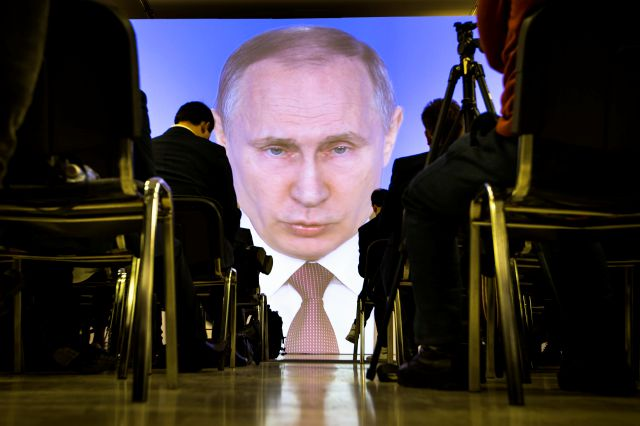 Russian President Vladimir Putin, shown on a large video screen, gives his annual state of the nation address in Moscow, Russia, Thursday, as journalists watch. Associated Press