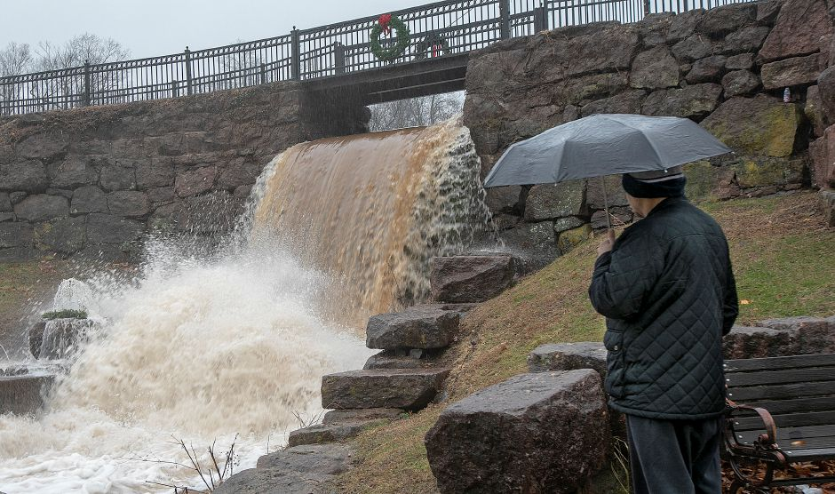 Robert LaHaye, of Meriden, watches as water gushes down the waterfall at Hubbard Park during heavy rains in Meriden, Fri., Dec. 21, 2018. Dave Zajac, Record-Journal