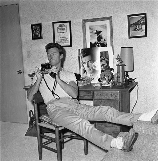 Away from the rough-and-tumble life of a Western TV star, actor Clint Eastwood finds his much-desired rest and quiet in his spacious Hollywood Hills home overlooking the San Fernando Valley, Oct. 25, 1965. He enjoys time in the den, comfortably attired, Clint studies a new camera he has just bought. (AP Photo/David Smith)