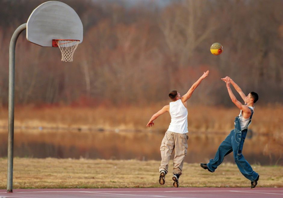 RJ file photo - Joe Baillargeon, 16, left, tries to block a shot by Stephen Grant, 15, at Habershon Field in Meriden on an unusually warm afternoon Dec. 16, 1998.