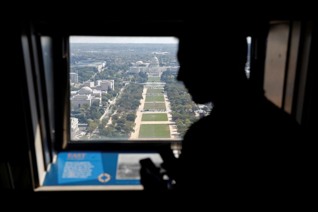 A visitor looks out toward the U.S. Capitol from the Washington Monument