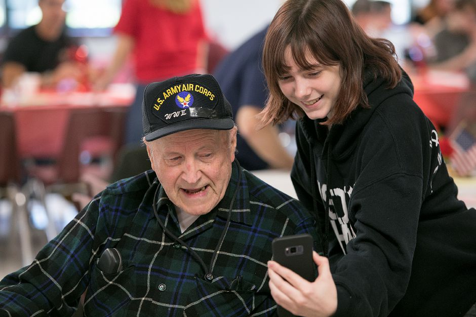 Student Mya LaMaster, 17, takes a selfie with WWII veteran Jim Hart, of Cheshire, during a Veterans Day Celebration at Cheshire High School, Friday, Nov. 10, 2017. | Dave Zajac, Record-Journal