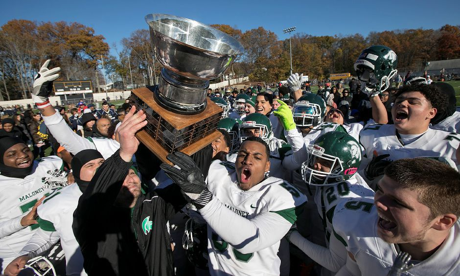 Maloney Spartans head coach Kevin Frederick and linebacker Darlin Lopez hoist the Stoddard Bowl trophy after defeating Platt 27-21 at Falcon Field in Meriden, Thursday, Nov. 23, 2017. | Dave Zajac, Record-Journal