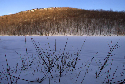 File photo - Saplings lay under a blue blanket of fresh snow on Crescent Lake as the setting sun grazes the top of Chauncey Peak, Jan. 9, 2001 .  The westward view is from the edge of White Trail at Giuffrida Park.
