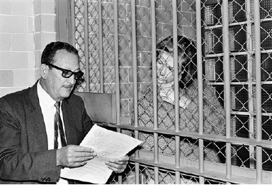 Sharon Kinne, of Independence, Mo., right, held in prison convicted of fatally shooting a man and wounding another, listens to translator Jose Gutierrez Suarez as he reads her ten-year sentence today at the preventive jail, Oct. 21, 1965, Mexico City. Mexico. The incident occurred at a Mexico City motel.  (AP Photo)