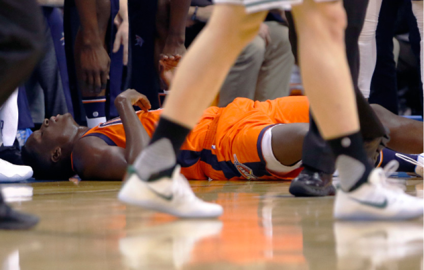 Oklahoma City Thunder guard Victor Oladipo lies on the court after an injury during a play against the Boston Celtics during the first half of an NBA basketball game in Oklahoma City, Sunday, Dec. 11, 2016. (AP Photo/Alonzo Adams)