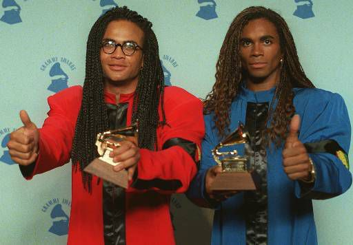 Rob Pilatus, left, and Fab Morvan of Milli Vanilli give the thumbs-up as they display their Grammys after being presented with the 1989 best new artist award in Los Angeles Feb. 21, 1990. They were later stripped of their award after being revealed as lip-synching poseurs. (AP Photo/Douglas C. Pizac)