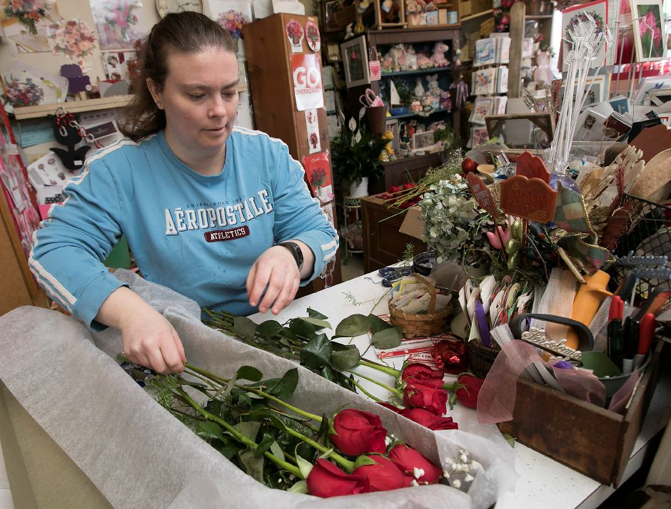 Amy Clark, holiday helper, gathers a dozen roses for a Valentine