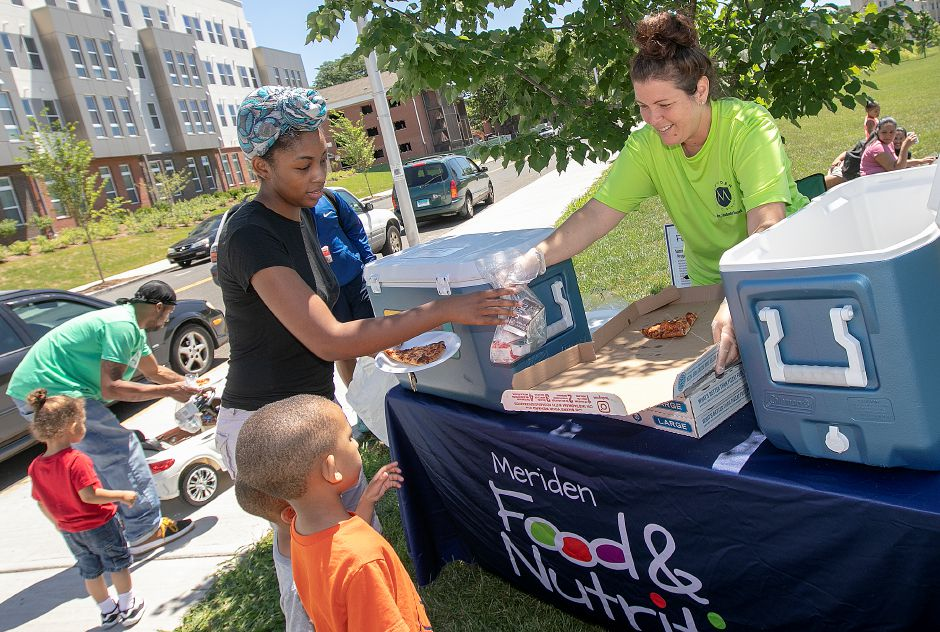 Kristina Horton, right, serves slices of pizza, juice and milk to Meriden resident Tanaeja Holmes for her children, Jordan Cyr, 2, and Christopher Cyr, 4, during the Meriden Summer Meals Program at the Meriden Green Thursday. Photos by Dave Zajac, Record-Journal