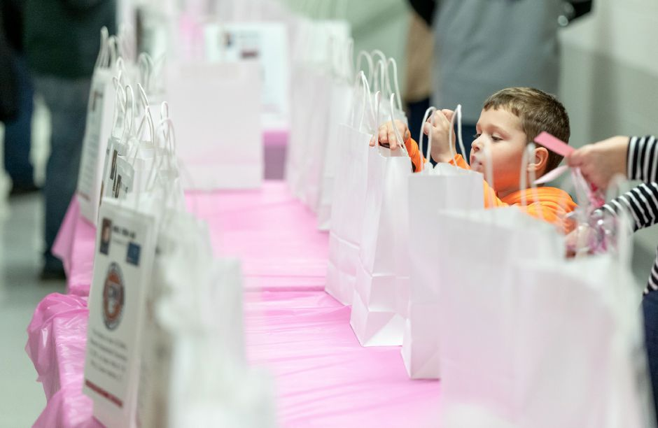 Kaden Shukis, 4, of Middletown, places tickets in raffle bags at a pasta dinner fundraiser for Berlin Police Officer Aimee Krzykowski for her medical expenses resulting from cancer treatment. The fundraiser was held at Berlin High School on Nov. 29, 2018. | Devin Leith-Yessian/Berlin Citizen
