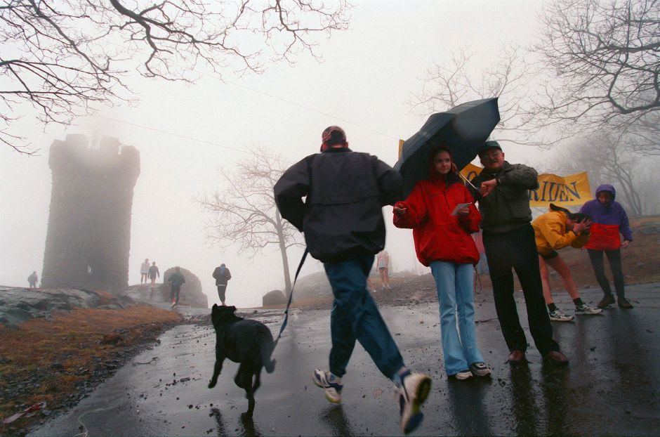 RJ file photo - Tradition Run volunteers Megan Harrington and Lou Bither check a runner and his dog in at the finish line of the event Jan. 24, 1999.