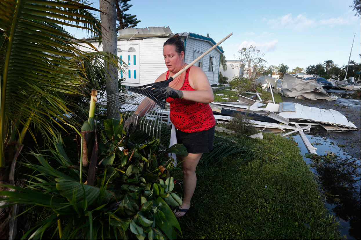 Karyn Chapman in the Naples Estates mobile home park, cleans up debris in front of her destroyed home, in the aftermath of Hurricane Irma, which passed through Sunday, in Naples, Fla., Tuesday, Sept. 12, 2017. (AP Photo/Gerald Herbert)