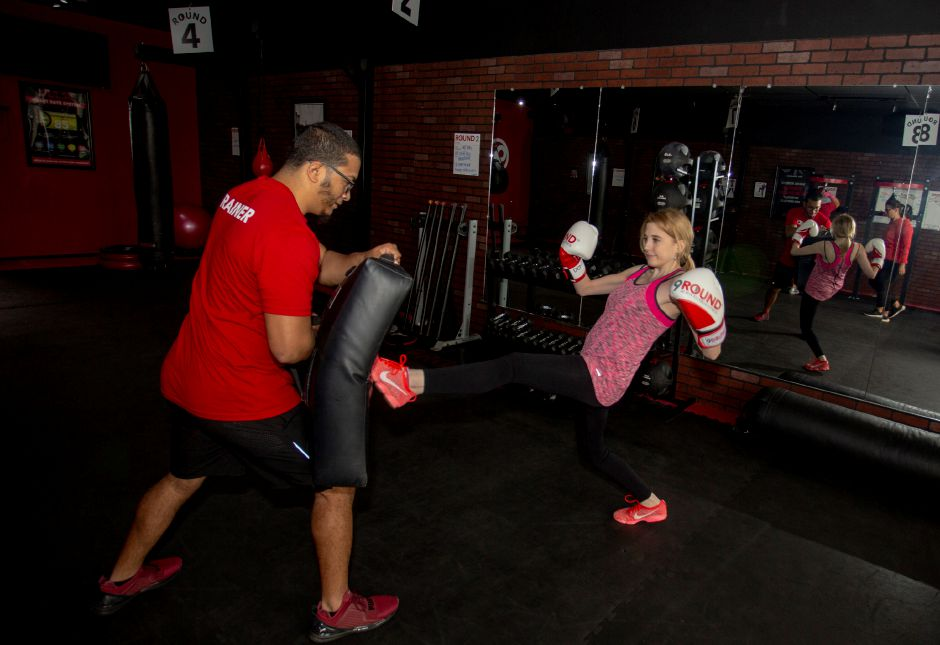 Record-Journal Digital Content Producer Ashley Kus, right, learns to kick with Christian Bagan of Waterbury at the 9Round Fitness facility in Wallingford. Richie Rathsack, Record-Journal