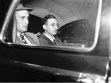 Julius Rosenberg, right, American-born engineer and New York manufacturer, sits in auto with FBI man enroute to federal house of detention in New York City, after his arraignment, July 17, 1950 on charges of conspiring to commit espionage. He is held in $100,000 bail. He was arrested earlier in day by the FBI and accused of recruiting for a Russian-financed atom bomb spy ring. (AP Photo/Tom Fitzsimmons)