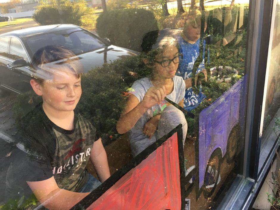 Green Acres Elementary School fifth-graders Russell Kieslich, 10, Fiona Gao, 10, and Jackson Burr, 11, decorate the window of Now Security Systems on Thursday, Nov. 2, 2017. | Lauren Takores, Record-Journal