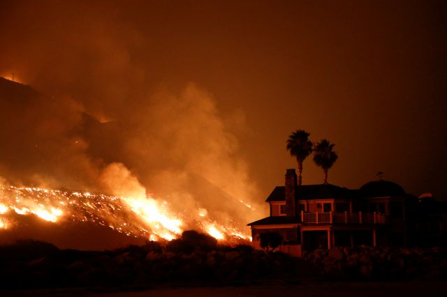A wildfire threatens homes as it burns along the 101 Freeway Tuesday, Dec. 5, 2017, in Ventura, Calif. Raked by ferocious Santa Ana winds, explosive wildfires northwest of Los Angeles and in the city