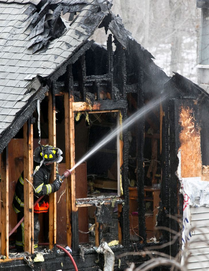 A firefighter douses a small hot spot on the house at 104 Hickory Lane in Cheshire after most of the fire had been extinguished Jan. 28, 2014. Firefighters had to spend quite a bit of time searching for smouldering pockets throughout the house which was heavily damaged. | Christopher Zajac / Record-Journal