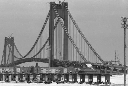 The Verrazano-Narrows bridge, spanning the mouth of New York Harbor, looms high over Staten Island buildings, August 29, 1964.  The far tower is in Brooklyn at the other end of what will be the world