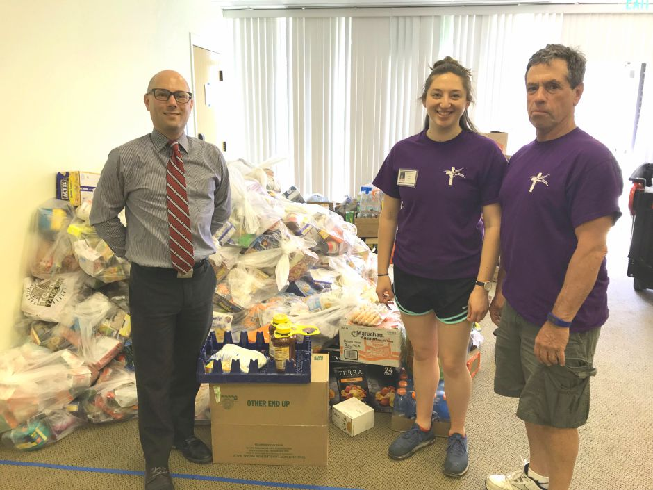 Vincent Contrucci, director of community service at Quinnipiac University, and Tori Shemo and Don Pursell, who are volunteers at Master's Manna Inc., a food pantry in Wallingford.