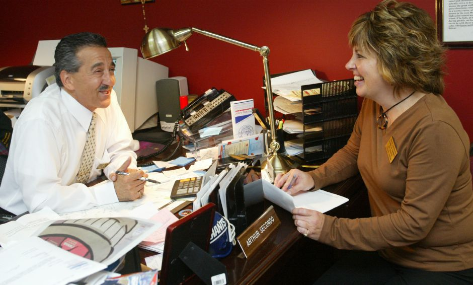 In this file photo, Art Secondo, former Southington chamber of commerce president, and former executive assistant Dee Violette discuss the days events in the office at Factory Square in Southington.