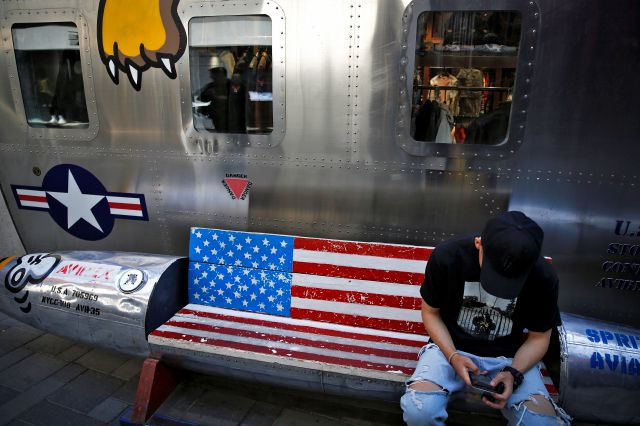A man browses his smartphone on a bench with a decorated with U.S. flag outside a fashion boutique selling U.S. brand clothing at the capital city