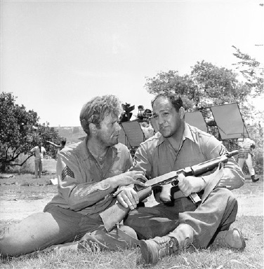 "Vic Morrow, star of ABC-TV's ""Combat"" series, and former heavyweight champion Rocky Marciano examine an automatic rifle on August 22, 1963 while a crew readies the set for filming behind them. Marciano plays a bit part in an upcoming show on the series. (AP Photo/David Smith)"