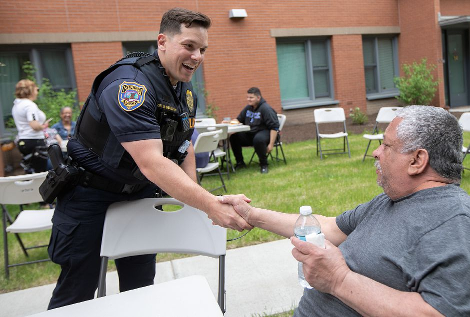 Officer Mike Shedlock greets Wilfredo Adorno, of Meriden, during a cookout in the courtyard behind 24 Colony St. in Meriden, on Friday. Downtown residents enjoyed a cookout with members of the police department and the NI unit as an ongoing effort to increase relationships between citizens and officers. Dave Zajac, Record-Journal