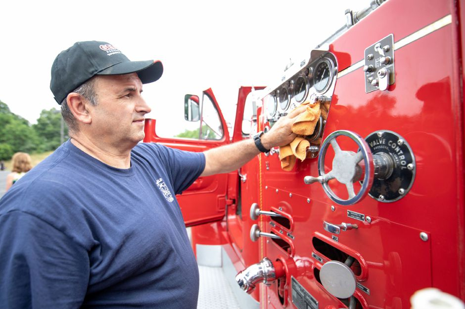 MIddlefield FIre Chief Peter Tyc wipes down one of their old engines at the Wallingford Fire Department