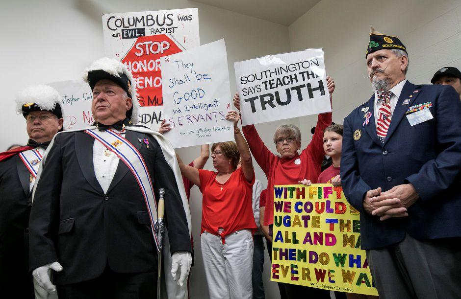 Protesters hold signs behind Knights of Columbus members, left, and Steve Pintarich, honor guard Southington Kiltonic Post 72, right, during a dedicaton and unveiling of a Christopher Columbus monument at Southington