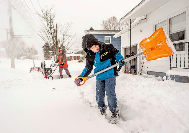Alando May, 7, shovels a path to the front door, while his grandmother, Virginia Slattery clears her driveway in Lewiston, Maine on Thursday, March 8, 2018.  A nor