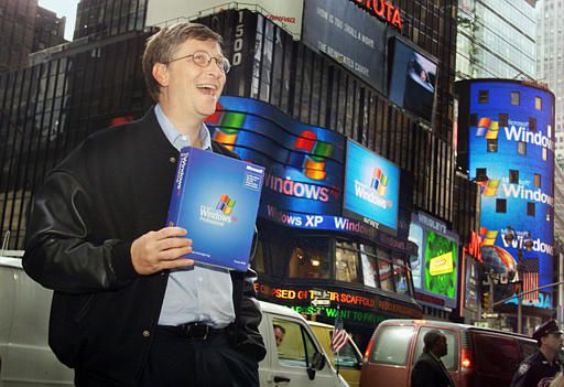 "Microsoft chairman Bill Gates stands in Times Square to promote the new Windows XP operating system Thursday, Oct. 25, 2001, in New York. Gates touted the software as the harbinger of a new era in more Internet-centric computing. ""Today it really is actually the end of the MS-DOS era,"" Gates said. Electronic Displays on the ABC studios, left, and the Nasdaq market site display the new Windows operating system. (AP Photo/Richard Drew)"