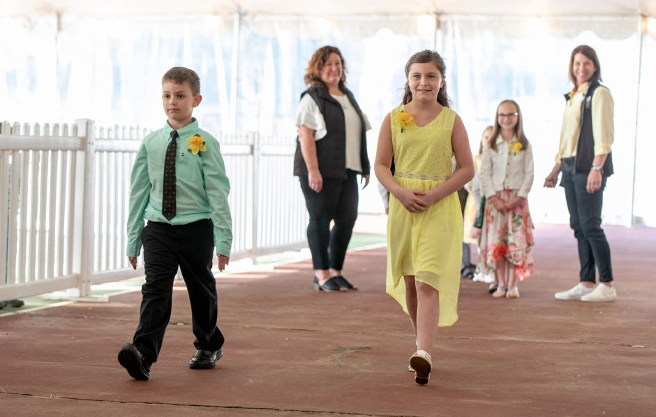 Bella Farina, 9, right, and Luke Pandiani, 9, of Hanover Elementary School, walk to the stage during the crowning ceremony for Miss Daffodil on April 24, 2019. Minutes later Mayor Kevin Scarpati would select one of the 9 elementary school girls to be crowned the head of the Meriden Daffodil Festival Parade on April 27. | Devin Leith-Yessian/Record-Journal