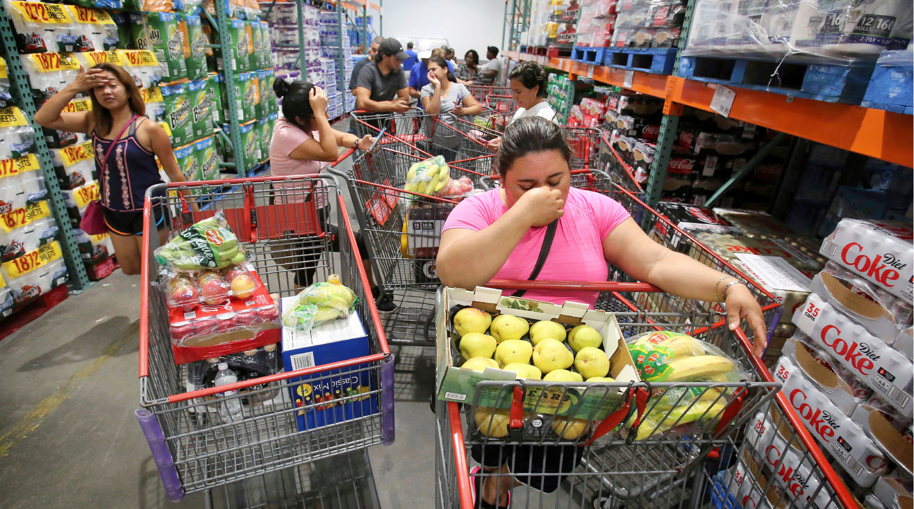 Shoppers wait in line for the arrival of a shipment of water during preparations for the impending arrival of Hurricane Irma, Wednesday, Sept. 6, 2017 in Altamonte Springs, Fla.  Irma roared into the Caribbean with record force early Wednesday, its 185-mph winds shaking homes and flooding buildings on a chain of small islands along a path toward Puerto Rico, Cuba and Hispaniola and a possible direct hit on densely populated South Florida.  (Joe Burbank/Orlando Sentinel via AP)