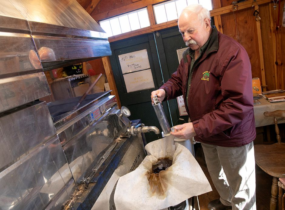 Michael Karabin of Karabin Farms checks the temperature of syrup after boiled in an evaporator in his sugarhouse at the Southington farm, 894 Andrews St., Tues., Mar. 19, 2019. Dave Zajac, Record-Journal