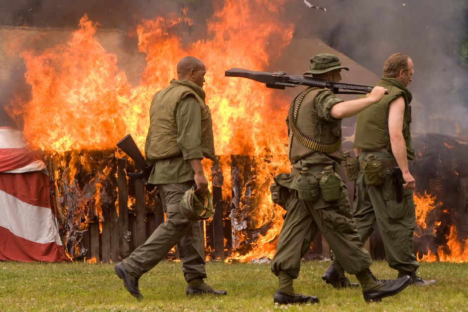 American flags burn in a pyre as Mark Harding, left, of Meriden, Gary Cosgrove, center, of Wallingford, and Jim Marut, right, of Meriden, take part in a war re-enactment during the 11th Annual Watch Fire Flag Retirement Ceremony at American Legion Post 45 in Meriden June 13, 2010. Over 6000 worn, tattered, faded and torn flags were retired during the ceremony attended by about 200 people. Harding and Marut are members of the Polish Legion of American Veterans and Cosgrove is a member of the American Legion. (dave zajac photo)