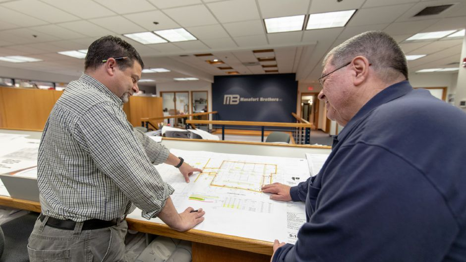 Workers look at site plans inside the Plainville headquarters of Manafort Brothers Incorporated on New Britain Avenue. The demolition and construction company is celebrating its 100th anniversary. | Devin Leith-Yessian/Plainville Citizen