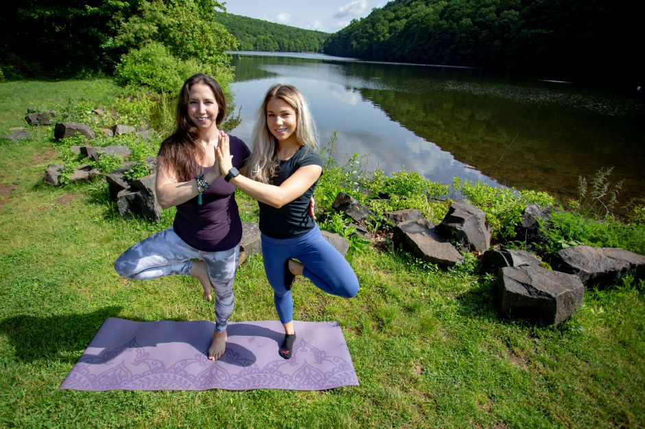 Brianne Barrett, owner of Bhogah Yoga School in Wallingford, shows Healthy Living writer Kristen Dearborn some yoga techniques at Guiffrida Park in Meriden May 31, 2019. Barrett will lead several yoga classes in conjunction with the Meriden Parks & Recreation Department over the summer at Hubbard Park, Guiffrida Park and the Meriden Green. | Richie Rathsack, Record-Journal
