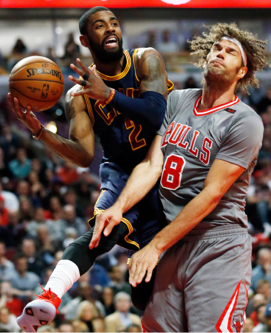 Cleveland Cavaliers guard Kyrie Irving, left, looks to pass against Chicago Bulls center Robin Lopez during the first half of an NBA basketball game Thursday, March 30, 2017, in Chicago. (AP Photo/Nam Y. Huh)
