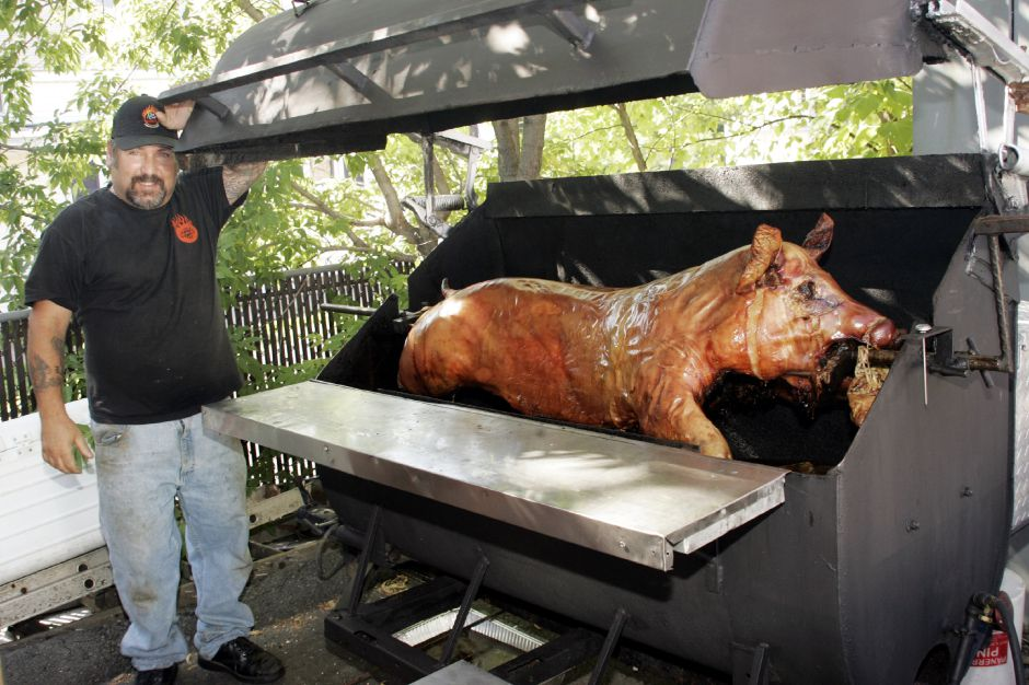 "Frank Petrone, co-owner of Pigout BBQ on Eden Ave. in Southington Sat., Aug. 14 with one of the roast pigs during their ""Pigstock"" event."
