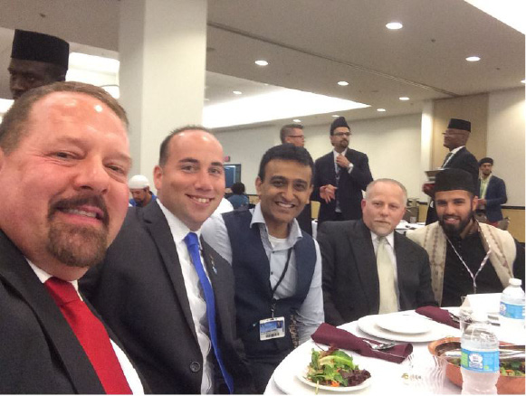 Ted Hakey, at left, sits next to Meriden Mayor Kevin Scarpati at Ahmadiyya Muslim Community USA's 68th annual convention last weekend in Pennsylvania. Also pictured is Zahir Mannan, at right, who serves as community outreach director for the Baitul Aman mosque in South Meriden. | Photo courtesy of Twitter