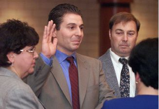 Meriden City Clerk Irene Masse, right, swears in Mark Benigni as the new Mayor of Meriden as his parents, Gail Benigni, left, and Jack Benigni second from right, stand on the stage at Edison Middle School with him December 3, 2001. FILE PHOTO.