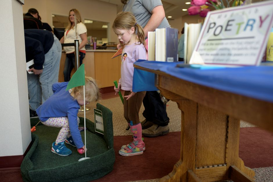 From left, Alice Knickerbocker, 3, and Jane Knickerbocker, 5, run the course with their father Jon. The Wallingford Public Library set up a mini-golf course on Saturday for ages 5+. Proceeds would benefit the library. Monica Jorge/Special to the Record-Journal